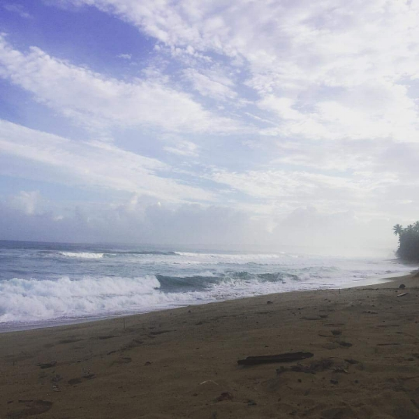 Photo Description: Waves on a sandy beach in Puerto Rico with a blue sky sprinkled with clouds above.