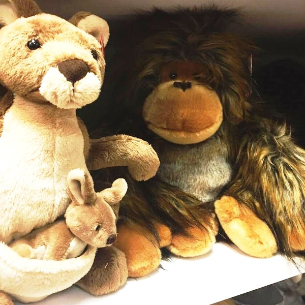 Picture Description: A family of stuffed animals, a Kangaroo with a baby in its pouch, and a monkey, smile at the camera from a white shelf.
