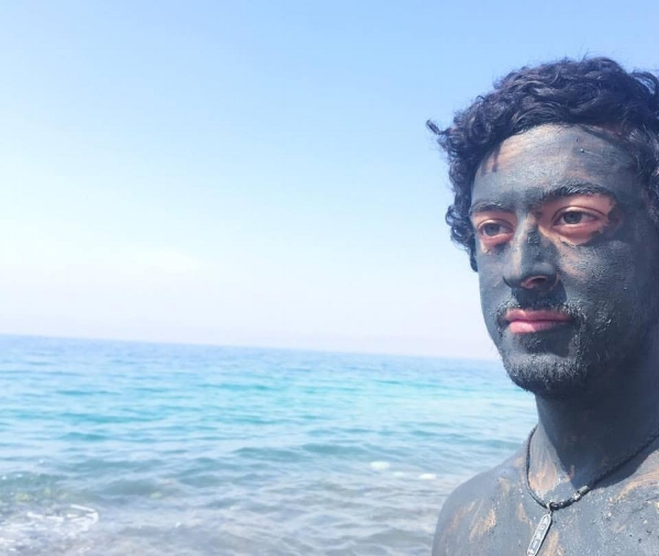 Photo Description: a man stares out, his shoulder to forehead covered in black Dead Sea mud, and the blue Dead Sea and sky surrounding him.