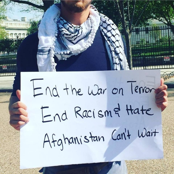 "Photo Description: a headless male with a slight beard holds a sign that reads ""End the war on terror. End racism and hate. Afghanistan can't wait"" in front of the White House fence."