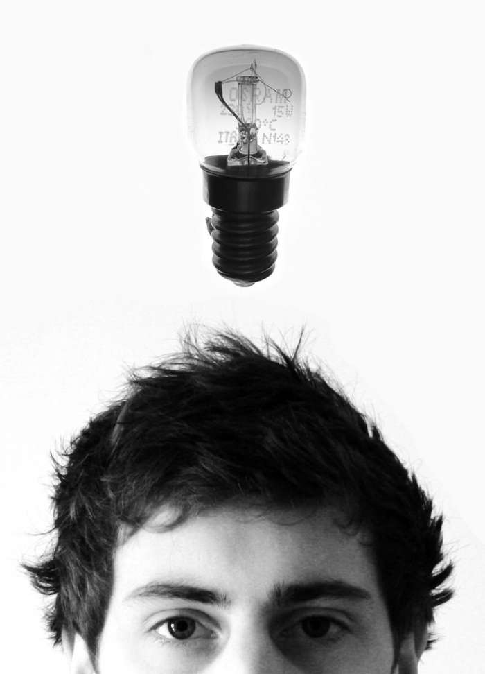 Photo Description: A lightbulb hovers above a man's face. The man's face is cropped from the bridge of the nose and down so you only see the eyes, and above.