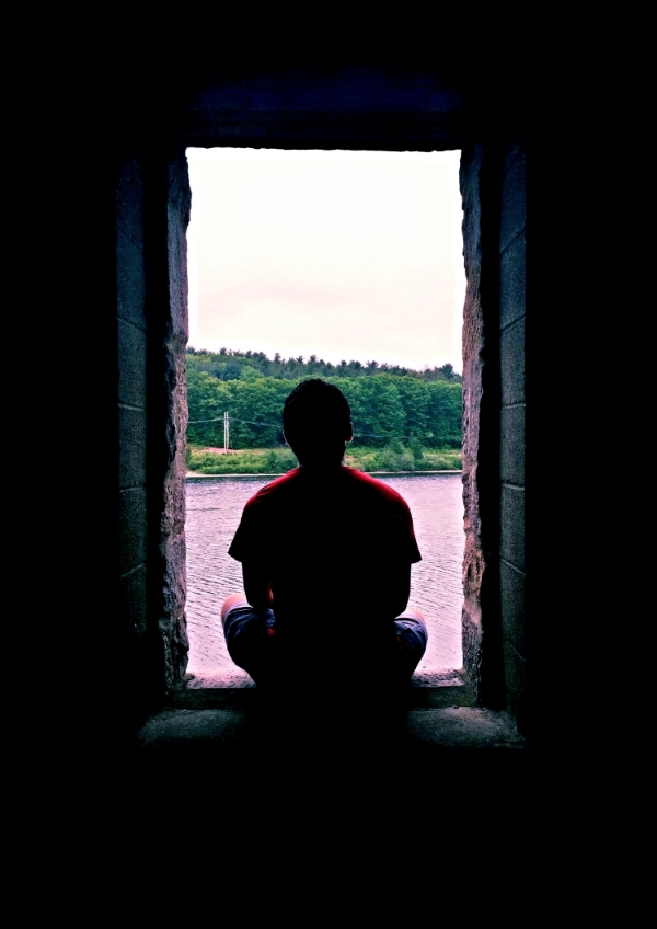 Photo Description: The rear silhouette of a person sitting, cross-legged, in a doorway, wearing a red t-shirt and blue shorts.  They look out over a river, immediately before them, trees and a road with a power line across the river, and the sky above the trees, somewhat grey. The doorway in which they sit allows little light in, illuminating only the rugged-cut stone doorway and cinder block room  most near the person.  The rest of the room is black and provides a beautiful natural frame of the image.