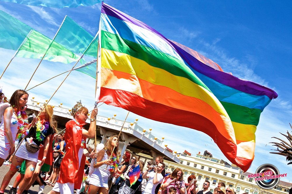 Photo Description; Many people stand on the street under blue skies with wispy clouds. A person marches center left holding a large rainbow flag which fills almost half the picture, much larger than the person holding it. Some other people march behind with green triangle flags.
