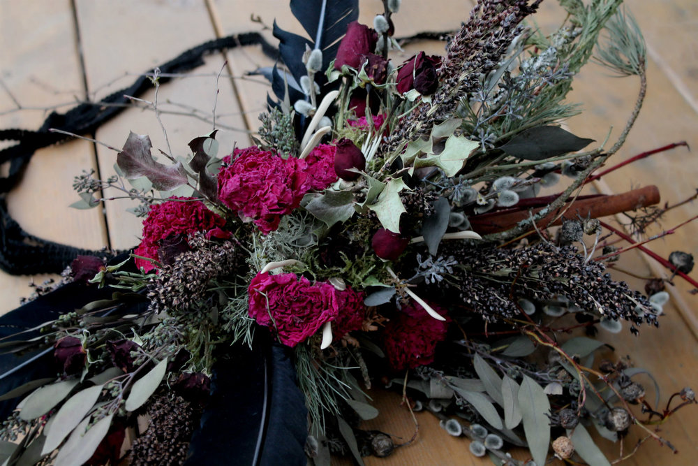 A Salem, Massachusetts bridal bouquet featuring peonies, black turkey feathers, cinnamon bark, dark grains and rosehips.