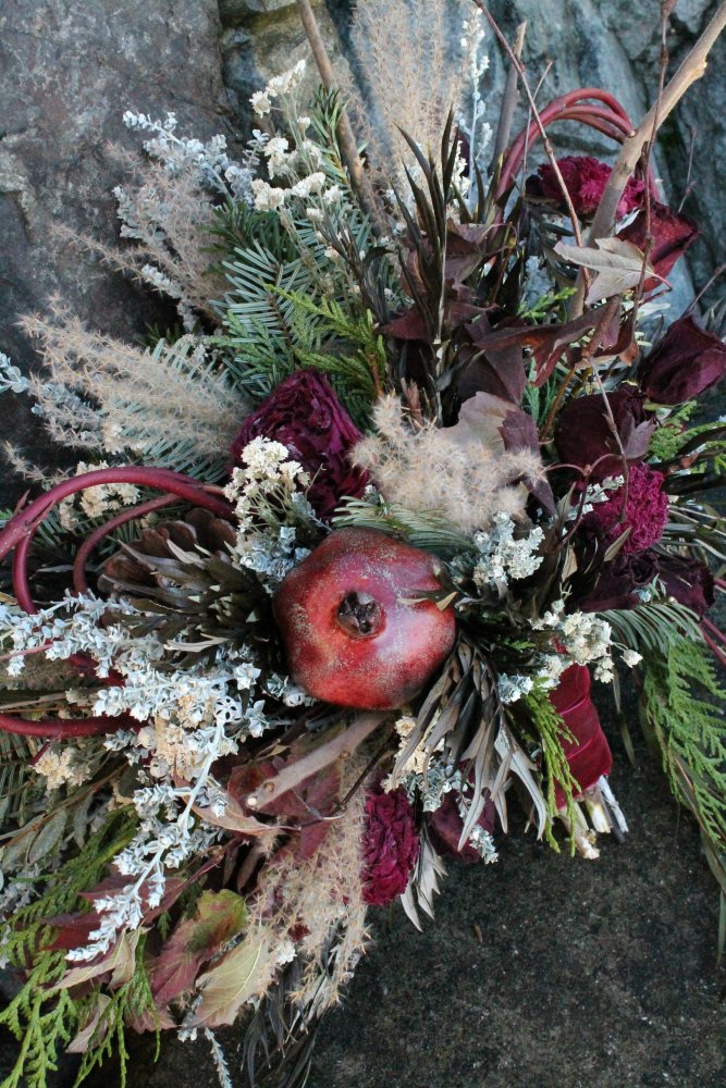 Ye Olde Christmas themed bridal bouqet featuring curled dogwood branches and a preserved pomegranate.