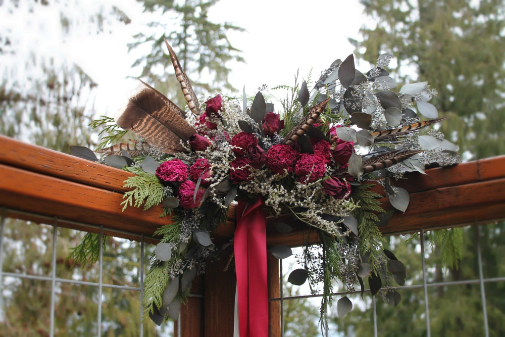 Foraged scarlet and woodland greenery bouquet  with turkey and pheasant feathers.