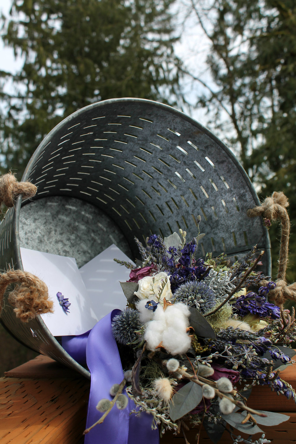 Slotted galvanized wedding guest card bucket with a Westerwisp bouquet at front.