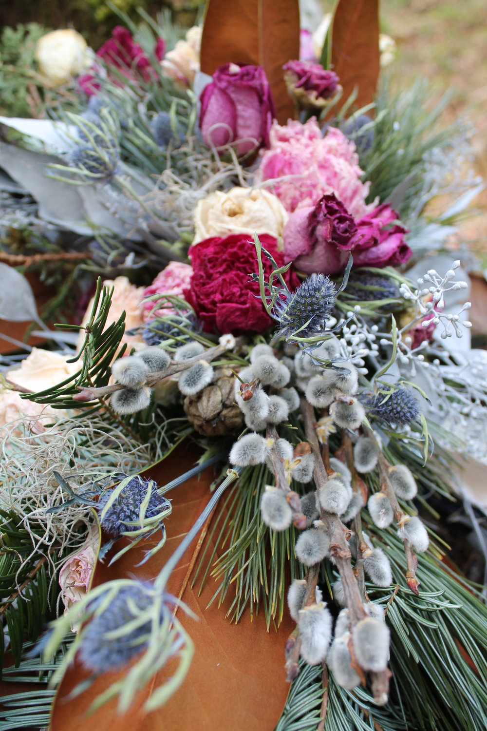 Spring Magnolia and Thistle bouquet. Featuring bronze magnolia leaves, woodland greeneries, pussywillow, blush, scarlet and pink peonies, cream roses, sea holly thistle and cream, gold and navy ribbons.