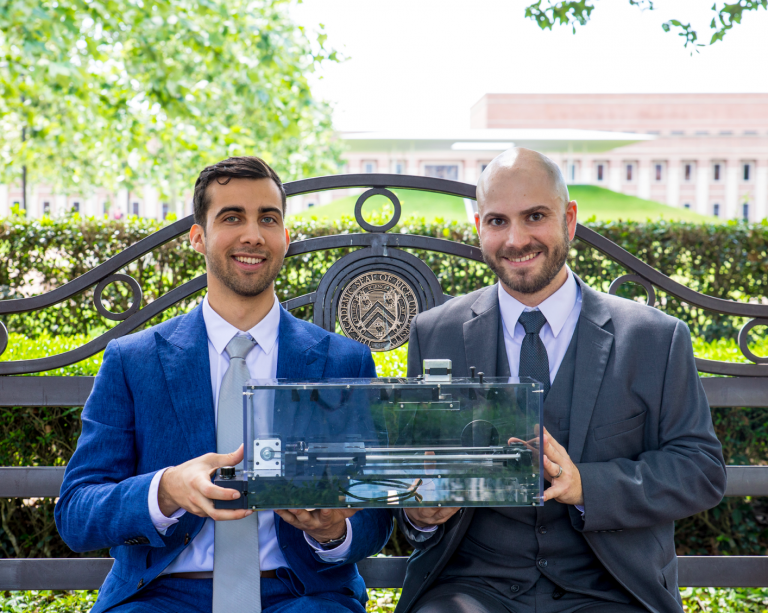 Left to right: Jonathan Bryan, an electrical engineering doctoral student and Peter Firth, CEO of Swift Coat hold a model of Swift Coat's nanoparticle deposition system on the Rice University campus in Houston, Texas. (Photo courtesy of Slyworks Photography.)