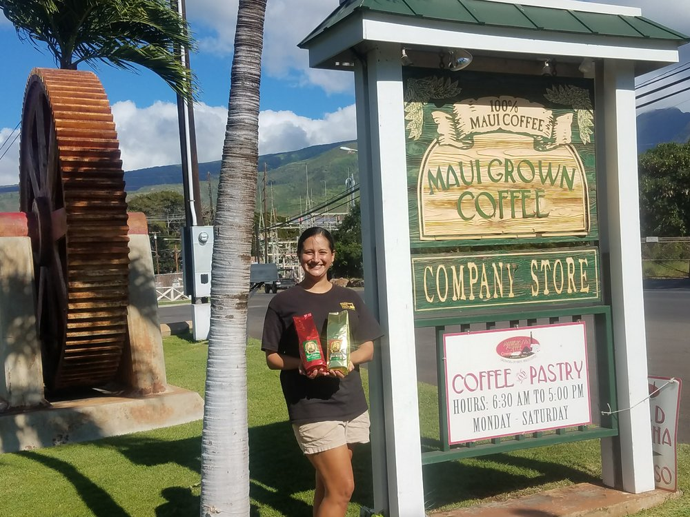 MauiGrown Coffee Company Store's Tara Buff shows off two of the store's popular holiday coffees.  Photo by Lee-Ann Panlasigui