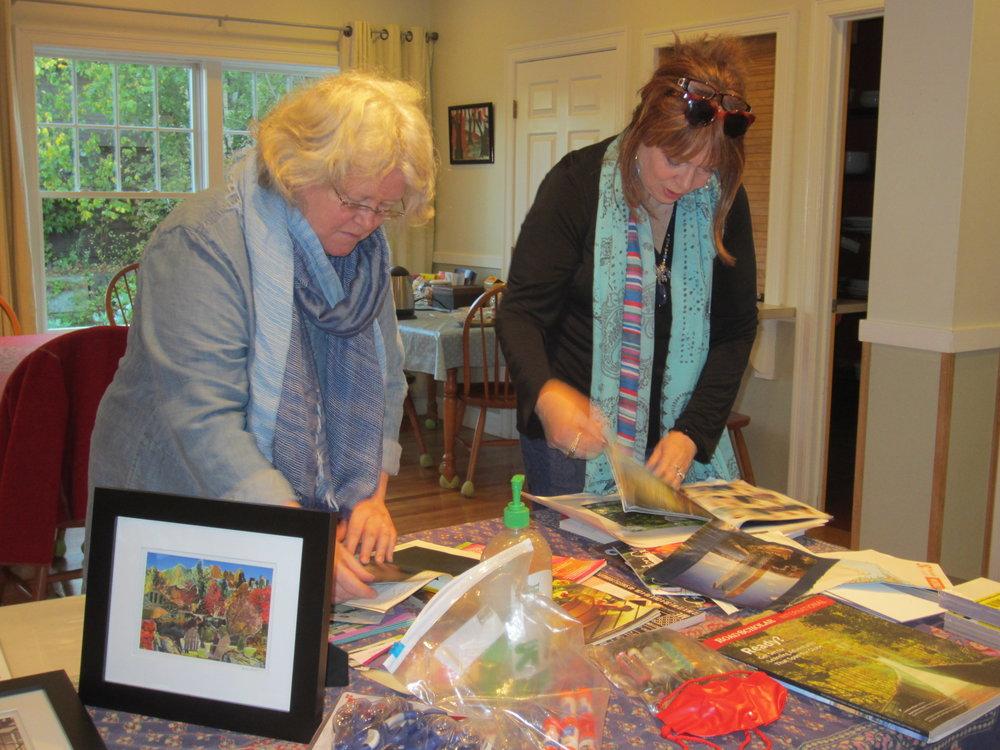 Two NoCa members select images to cut up for their collages.