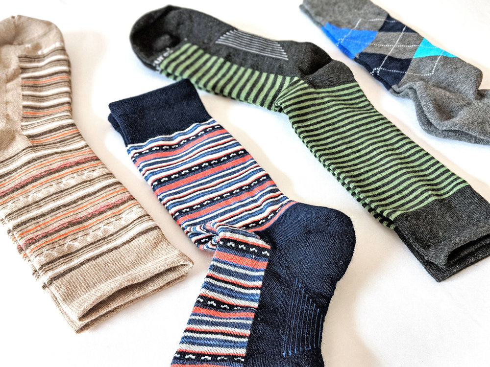 Feetures assorted crew sock styles, left two are women's, right two are men's - Photo Credit: The Sock Review