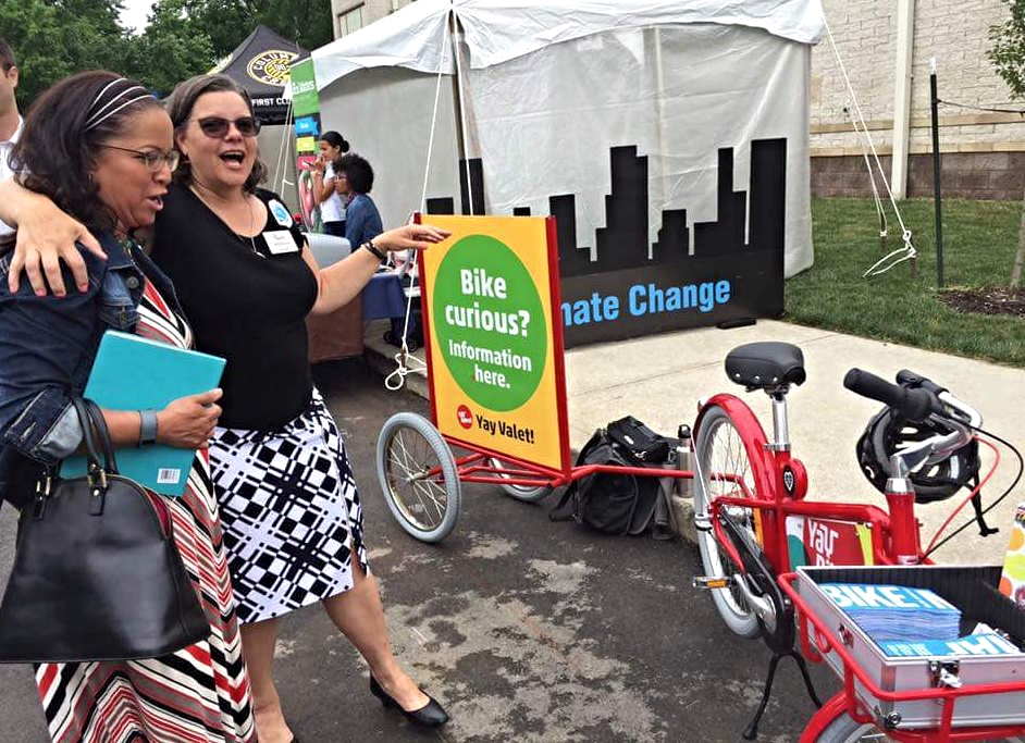 Catherine shows off our new outreach bike to Sandra López, Legislative Analyst, City Council Division of Community Engagement,at the Smart City award press release event.