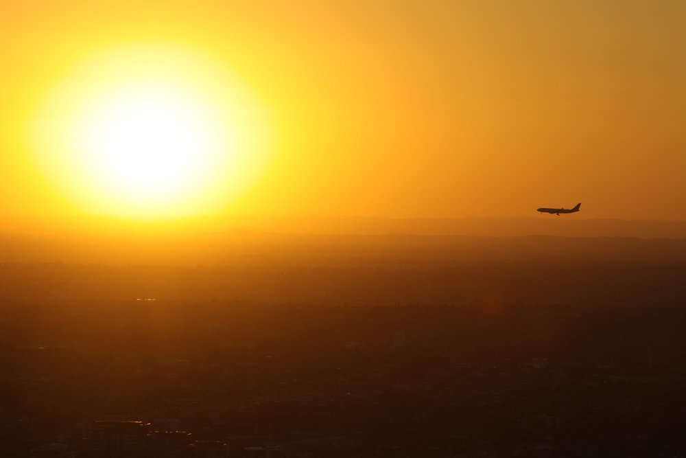 An aircraft coming in to land against the stunning sunset