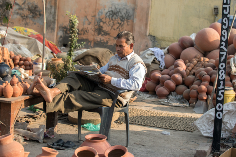 Potter reading the news, Agra, Uttar Pradesh, India