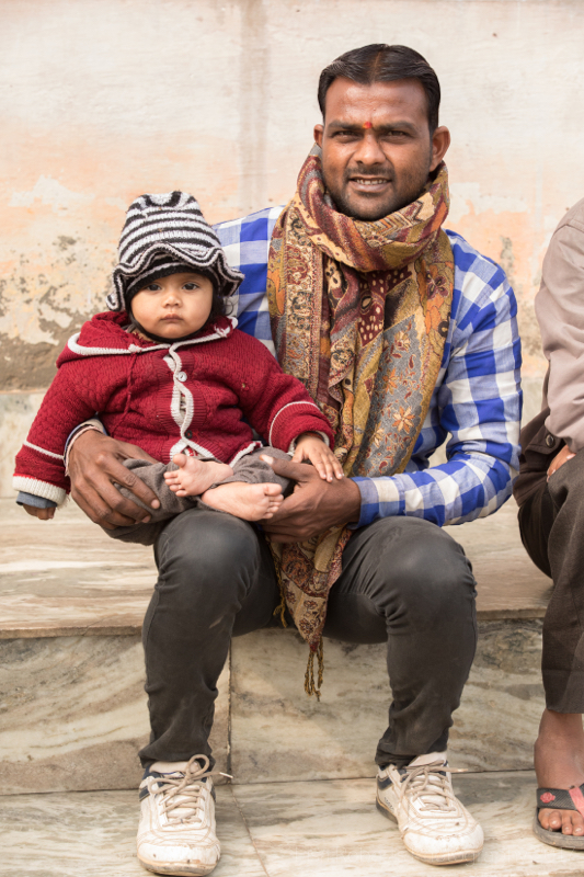 Man holding baby in striped hat, Mathura, Uttar Pradesh, India