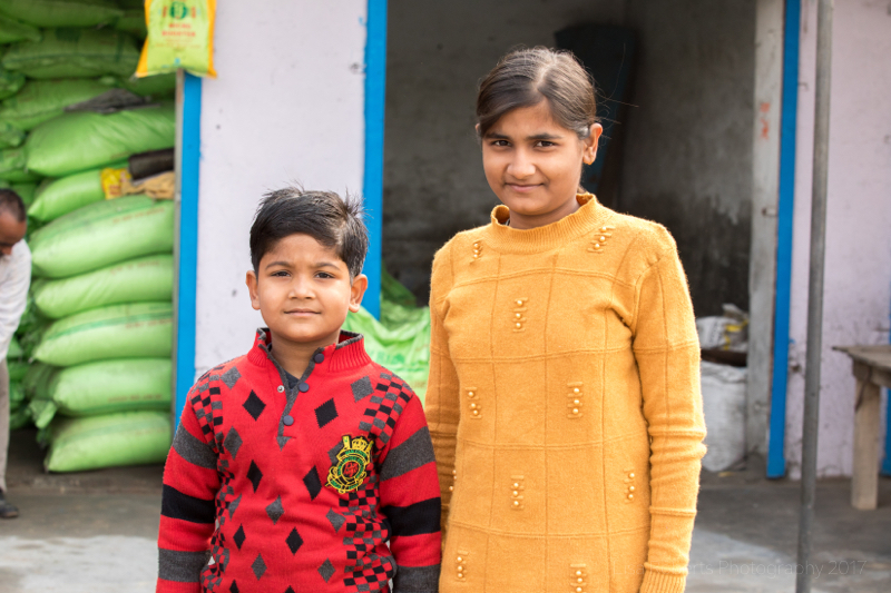 Boy in red & girl in yellow jumper, Boy holding baby with notepad, Mathura, Uttar Pradesh, India