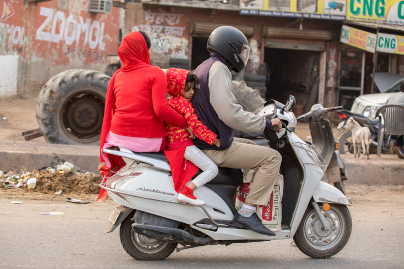 Sleeping child on moped, Gargaon, Haryana, India
