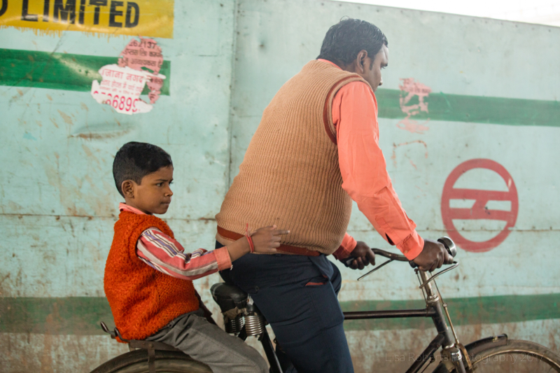 Boy on the back of his dad's bike, New Delhi, India
