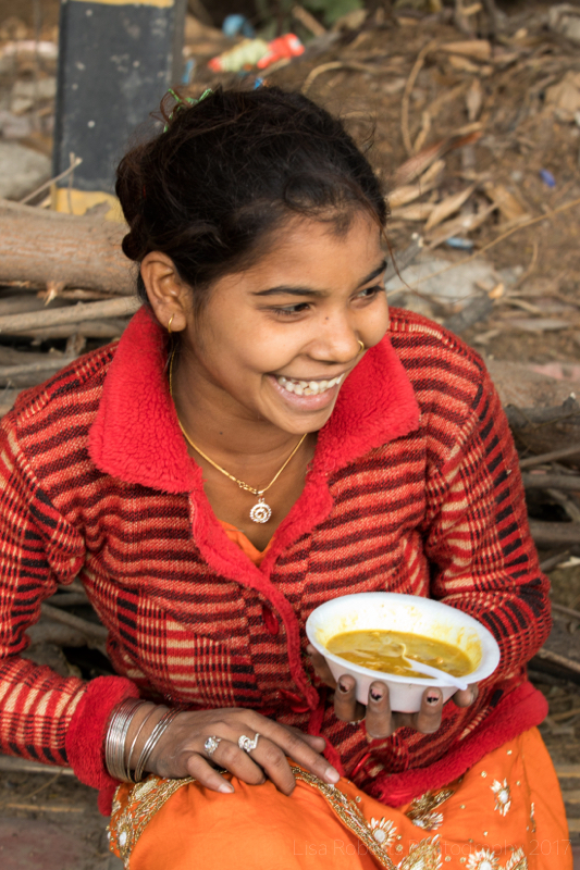 Happy girl with bowl of soup, New Delhi street slum, India