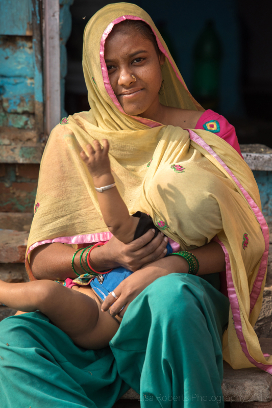 Young woman nursing her baby, New Delhi street slum, India