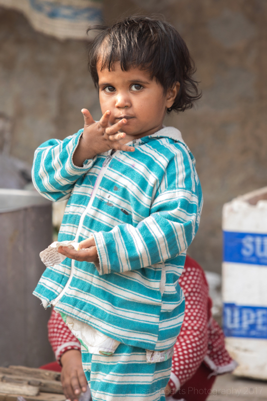 Child in blue & white striped top, New Delhi street slum, India