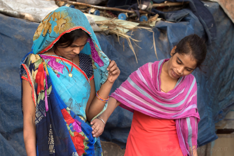 Comparing saris, New Delhi street slum, India