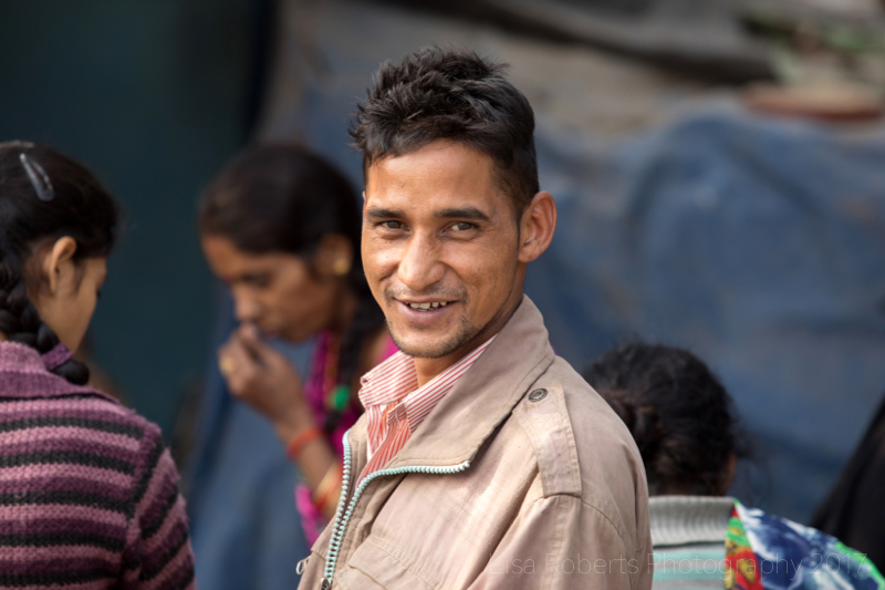 Man looking & smiling, New Delhi street slum, India