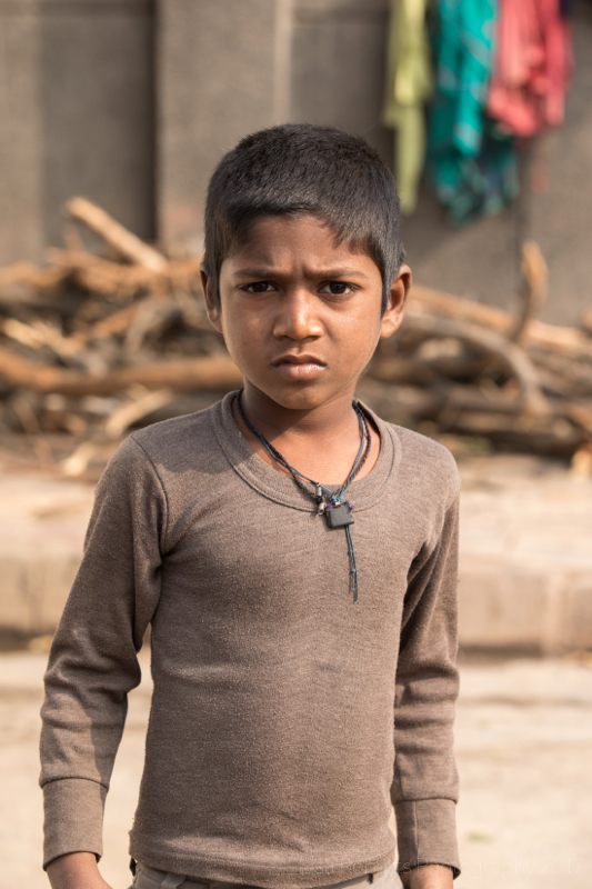 Young boy in brown top, New Delhi street slum, India