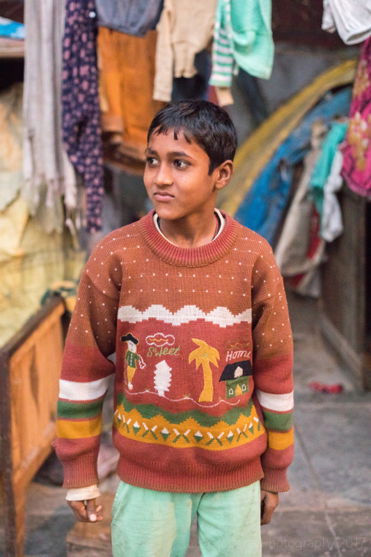 Boy in ironic jumper, Old woman in purple sari, New Delhi street slum, India