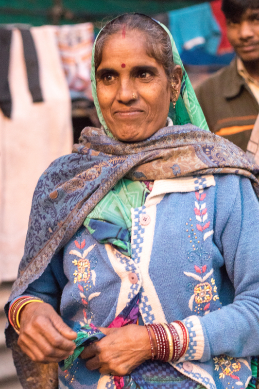 Elegant woman, Men in beanie hats, New Delhi Street slum, India