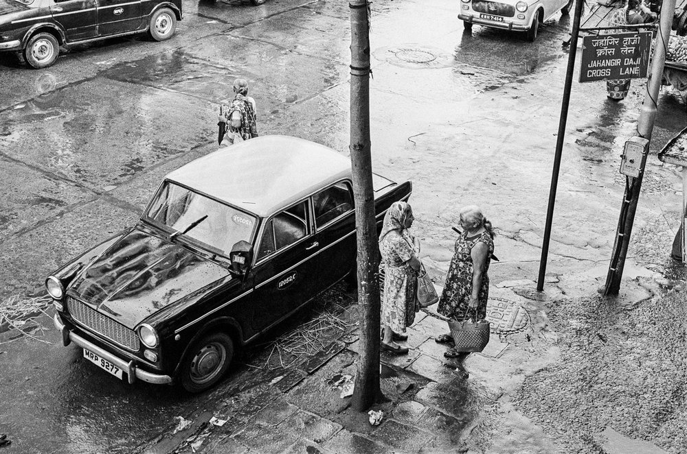 "Exchanging news at Jehangir Daji Cross Lane Bombay 1986 | Archival pigment print | 24"" x 35"""