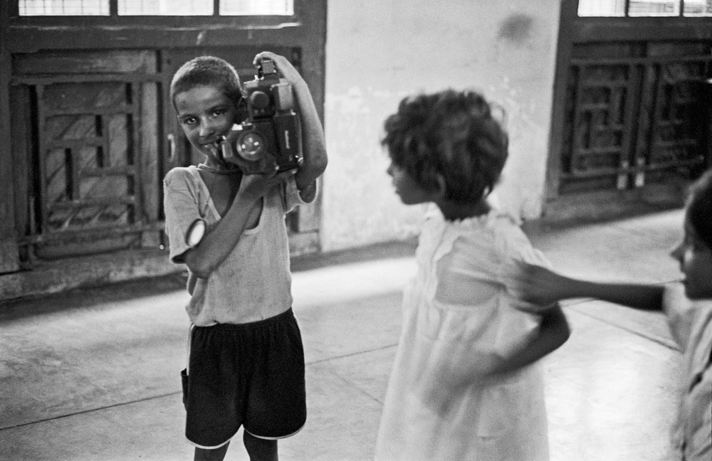 "Boy with camera, Bernard at Salaam Bombay! Workshop Bombay 1987 | Archival pigment print | 24"" x 35"""