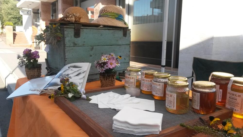 Siamo a metà Agosto, un ottimo raccolto e tanto miele da proporre. Parecchi clienti venivano in laboratorio a trovarci ma il nostro bisogno era quello di farci conoscere un po' di piu'....e così abbiamo preso la decisione.....un tavolino pieghevole, una tovaglia colorata, una vecchia arnia del nonno e il nostro miele......si parte!