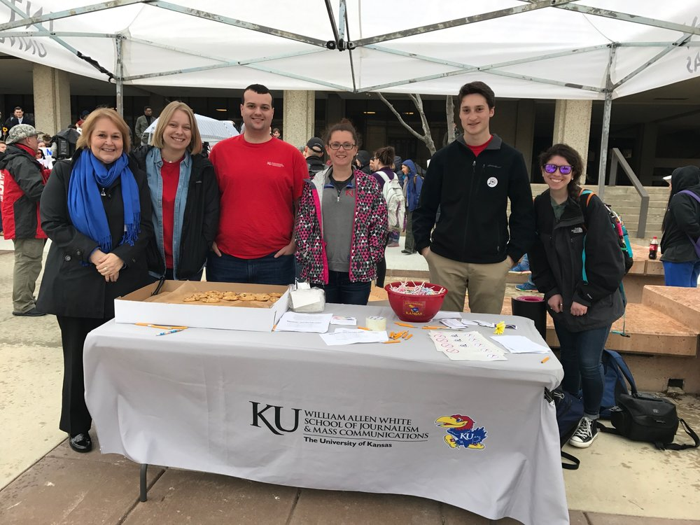 The Journalism Student Leadership Board set up a table on Wescoe Beach on April 4 for Hug A Newsperson Day. Board members invited students to take a quiz on fake news and handed out cards with tips on identifying fake news. They also handed out cookies, lollipops and stickers.