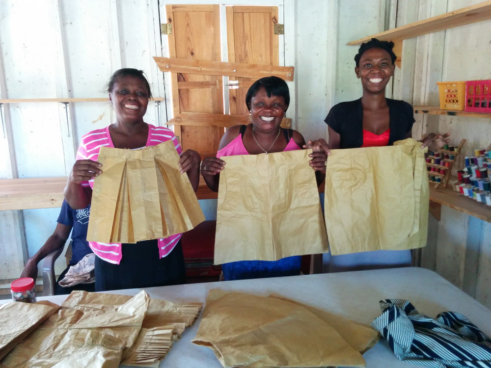 (Left to right) Jules, Terzilia, and Jemima are students in the Northwest Haiti Christian Mission's Môle-Saint-Nicolas sewing program. Here they're displaying their sewing paper skirts. They learn to sew by using sewing paper before they sew on fabric.
