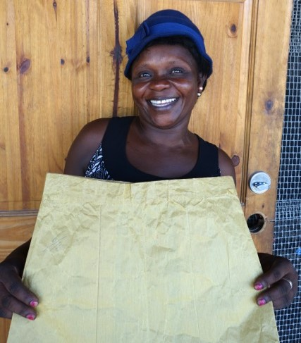 Terzilia is a student in our Mole St. Nicolas sewing program. She's holding up a sewing paper skirt, which is what they use to practice sewing on before using fabric.