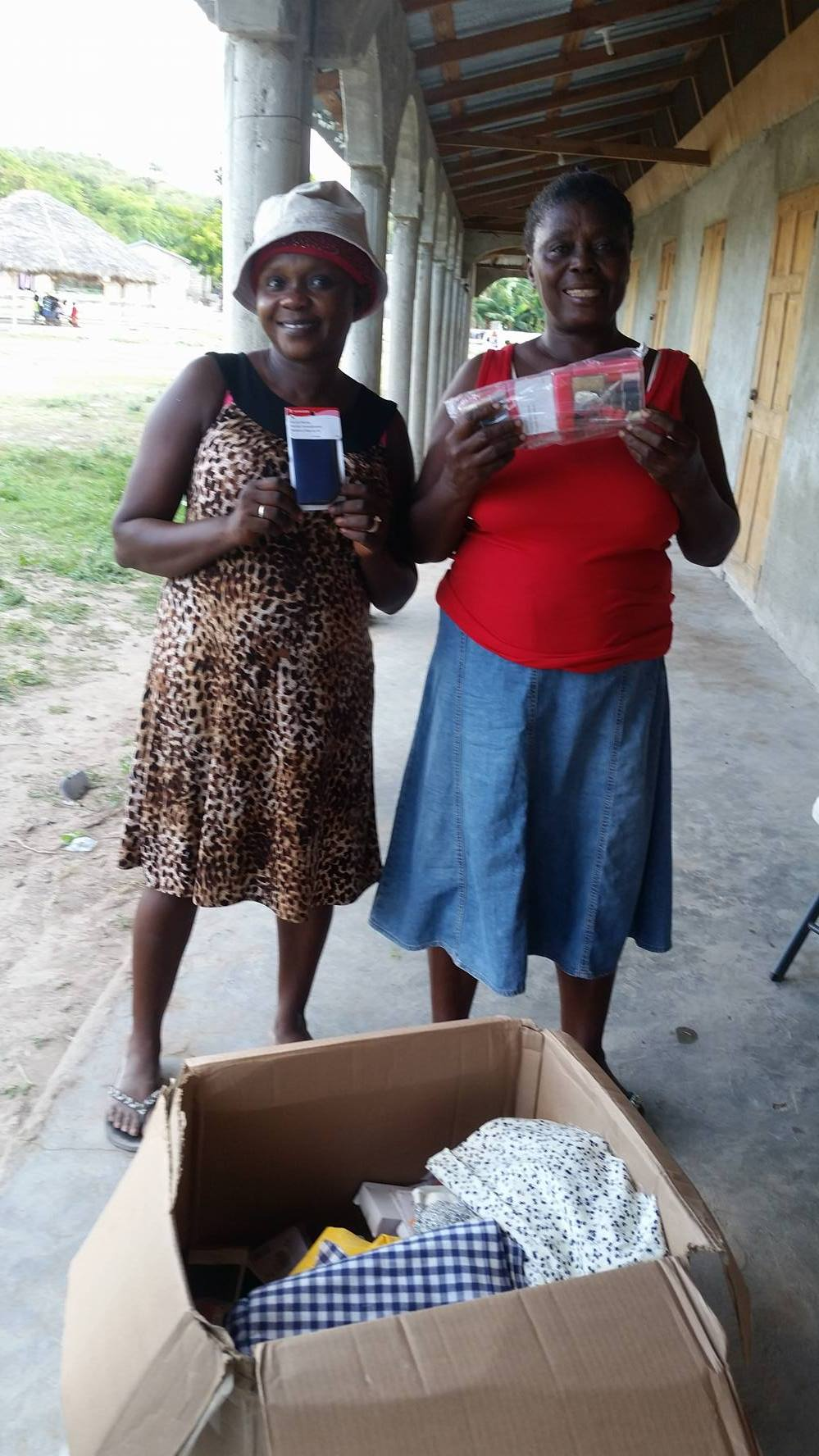 Terzilia and Jules, students in the Mole St. Nicolas sewing class, opening a box of donated sewing supplies.