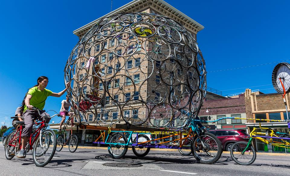 Volunteers moving a wheel dome by bike power. This sculpture was built by Free Cycles to be placed outside the Missoula Art Museum.