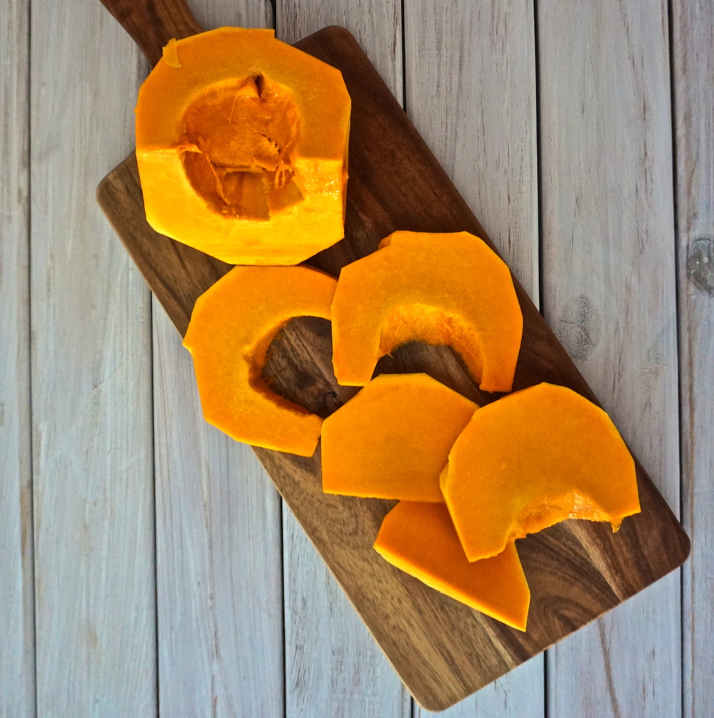 Delicious sliced pumpkin on wood chopping board