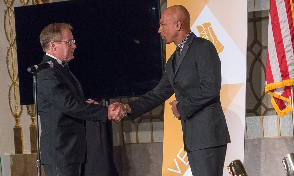 """On the left, President and CEO of Coalition to Salute America's Heroes, David Walker, shakes hands with Emmy-Winning Actor and U.S. Marine, Montel Williams. As the Leader of an organization with a mission to inspire other groups and the general public to participate in advocating for veterans, Walker proceeds to discuss the importance of the Vetty for Community. Williams follows with indicating why NVLSP has earned the award for the remarkable achievements made in year 2017. """