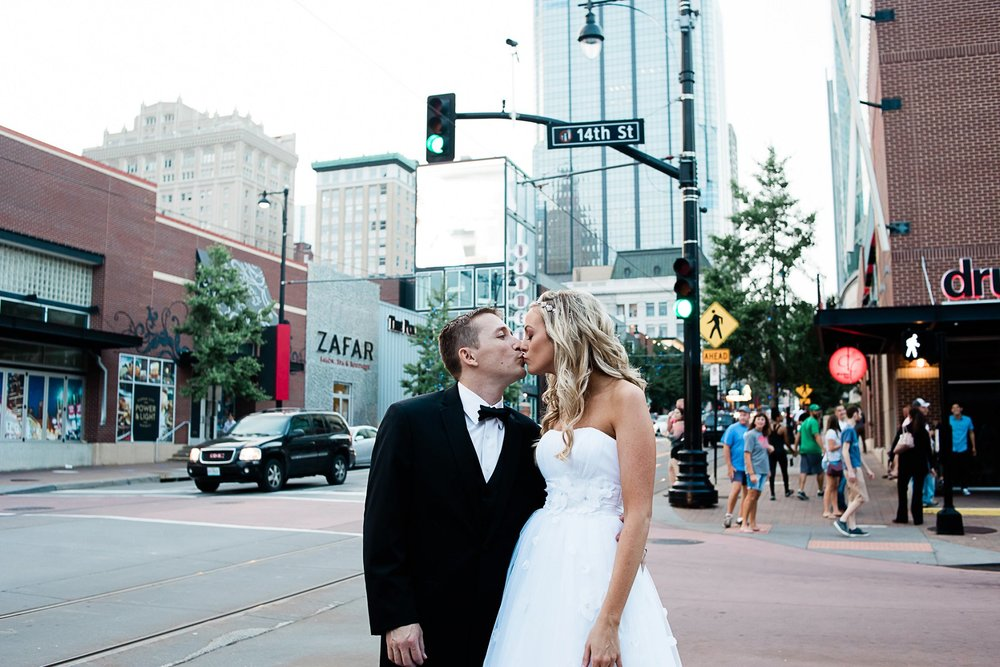 Bride and groom embrace on street in Kansas City by Merry Ohler
