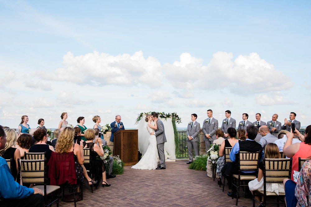 Bride and groom kiss while friends and family celebrate during ceremony on the Rooftop Terrace at The Oread Hotel in Lawrence, Kansas. Image by the best wedding photographer in Kansas City, Merry Ohler.