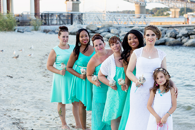 freight-shed-wedding-yorktown-virginia-photographers-bride-bridesmaid-pose-beach-front