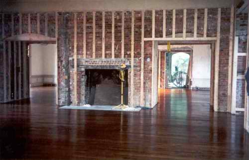 Now the fireplace has been opened back to its huge original size, the hardwood floor replaced and batten strips added to the walls, ready for the new paneling.