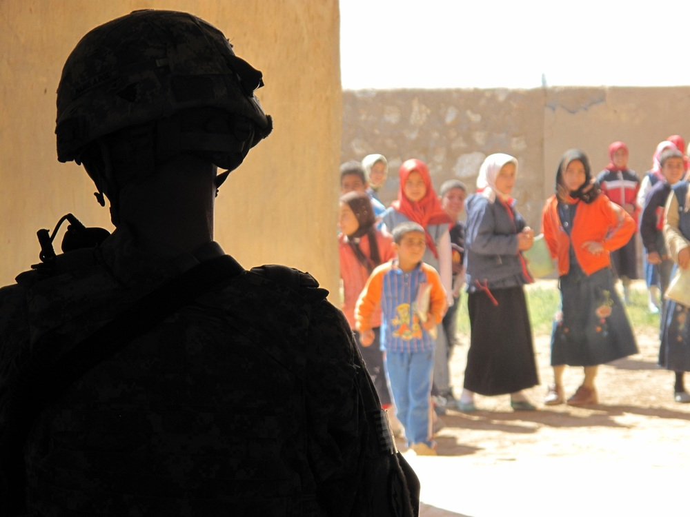 A U.S. service member patrols near a school during the war in Iraq.