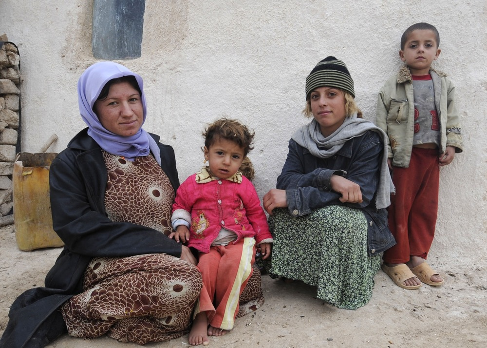 A woman and her young children sit near their home in Iraq.