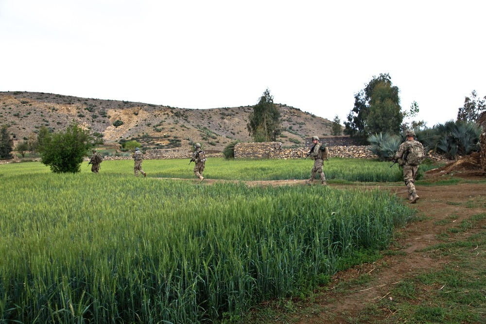 U.S service members patrol through farmland during the war in Afghanistan.
