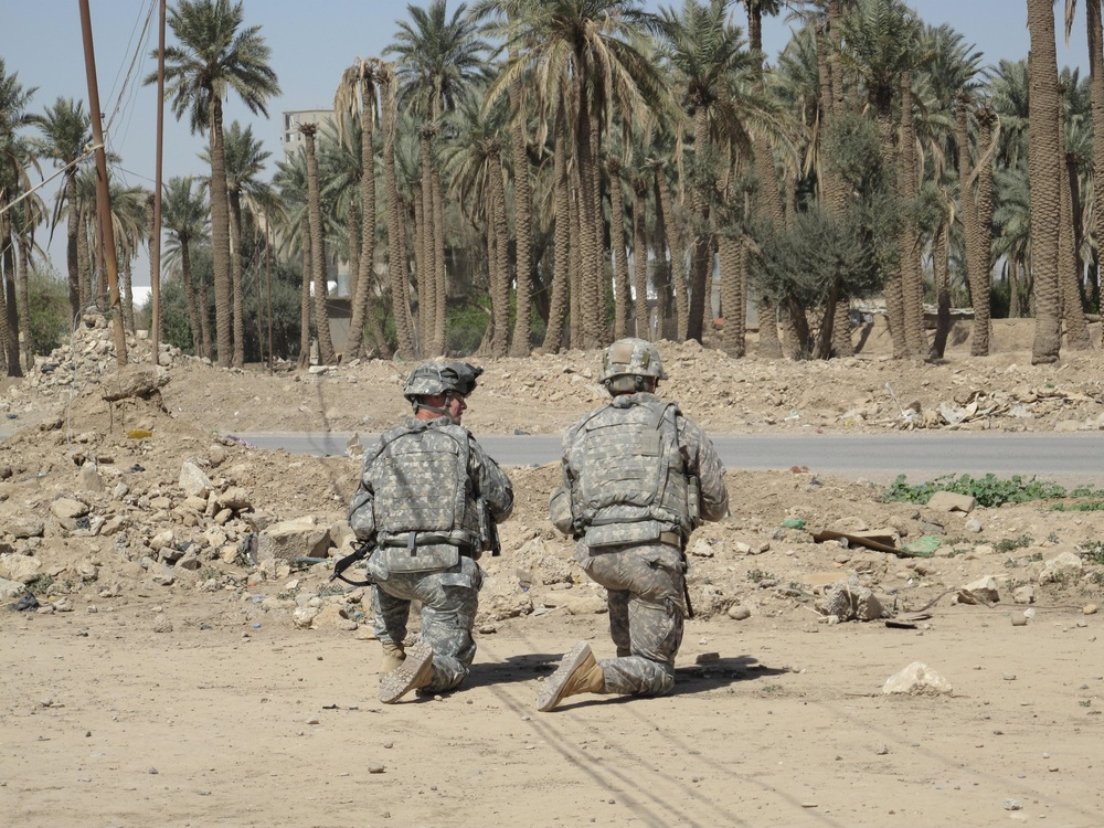 Service members from the United States kneel during a patrol in Iraq.