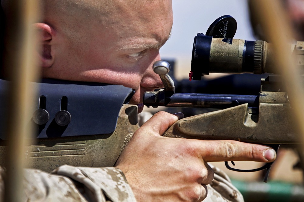 A U.S. Marine looks through the scope of his bolt-action rifle.